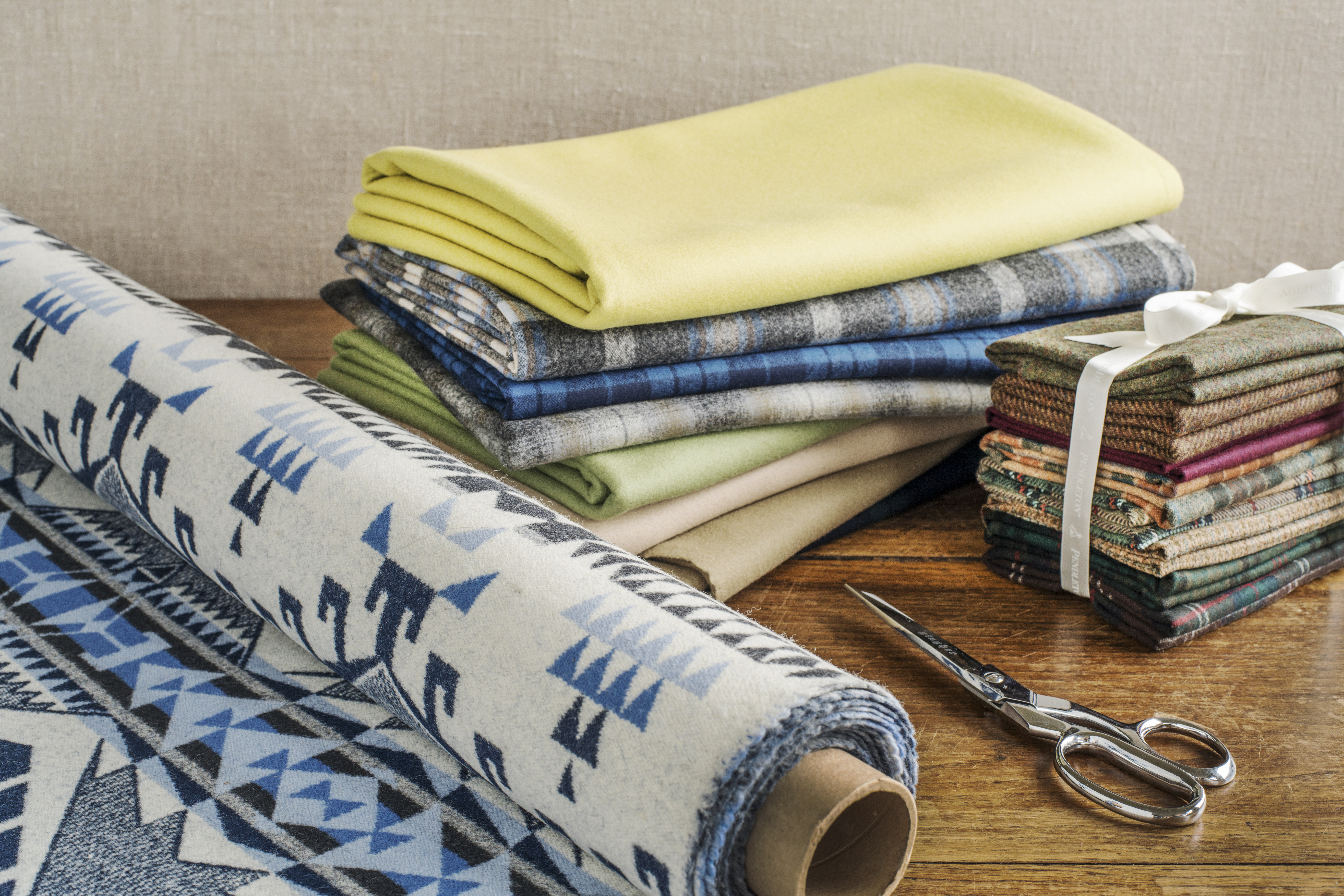 Roll of Pendleton fabric in blue and white, next to two stacks of folded Pendleton wool fabrics, scissors.