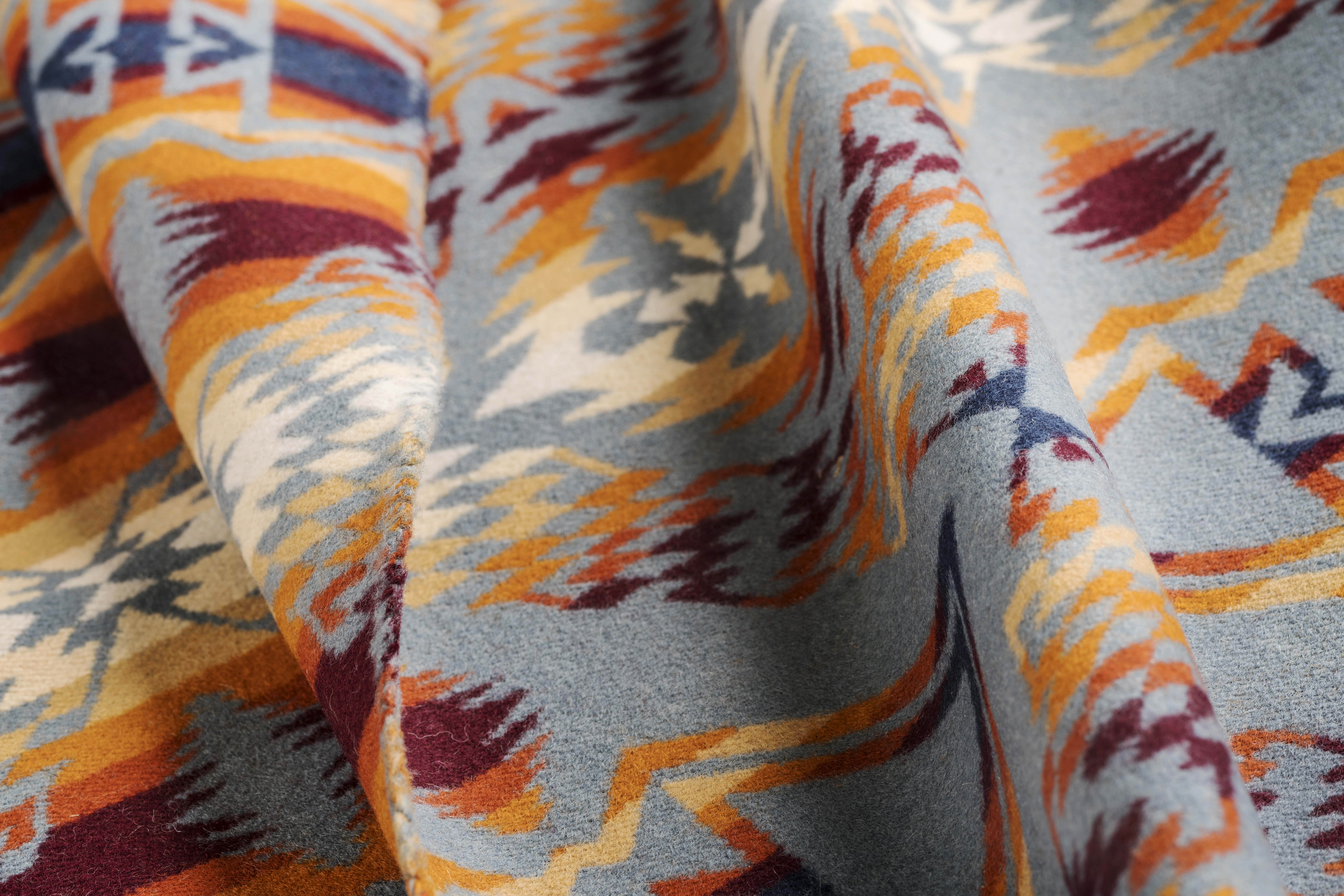 Photo of Pendleton jacquard wool fabric in a pattern of yellow, gold, red and white on a grey background.