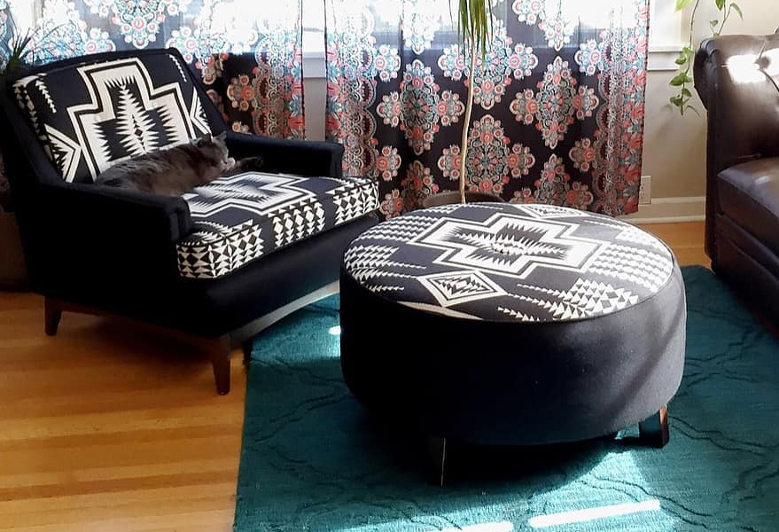 A chair and ottoman upholstered in Pendleton wool fabric in a black and white pattern. A grey cat named Peewee sleeps on the chair.