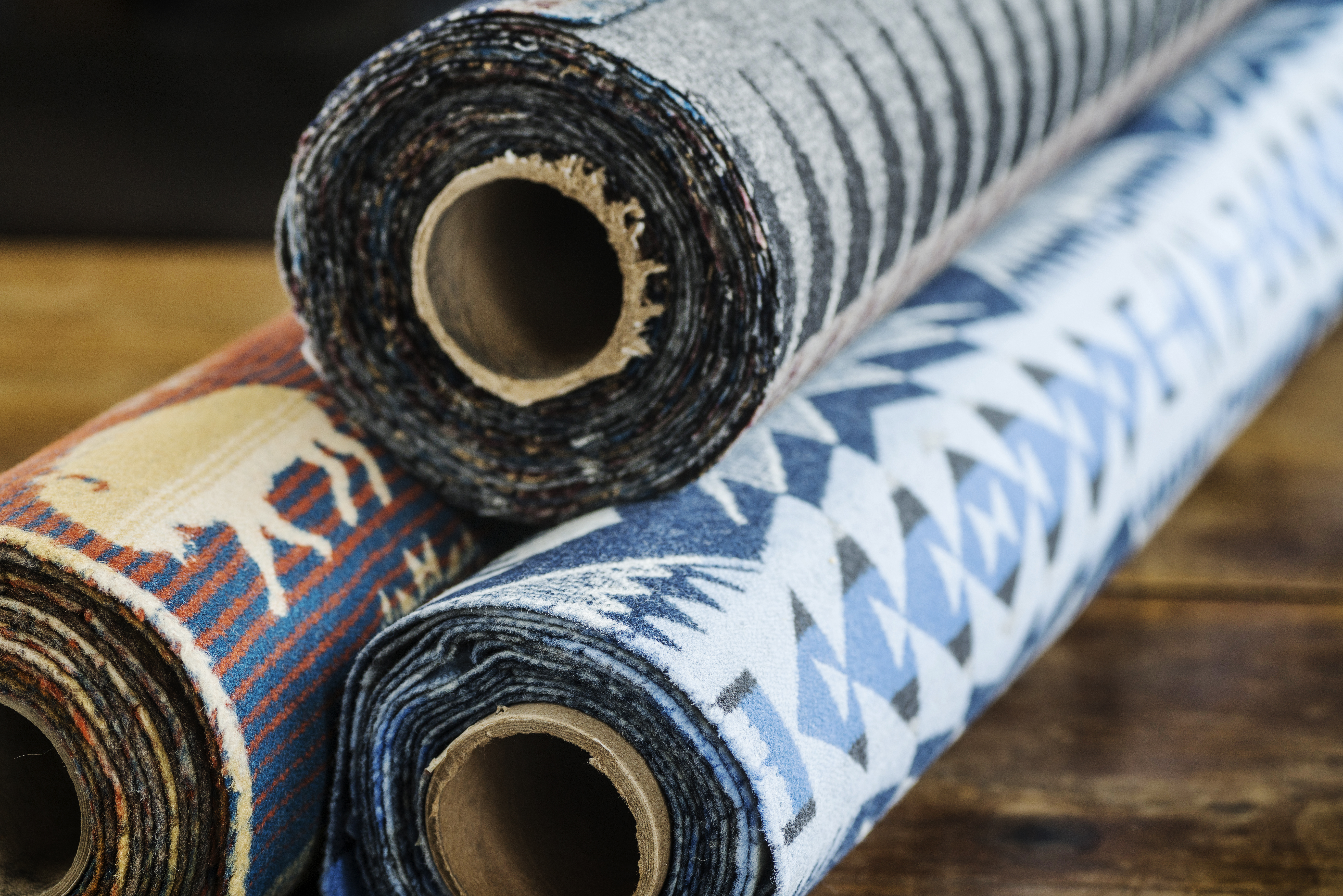 Rolls of Pendleton woolen fabrics in grey and black, shades of blue, and rust, navy cream.