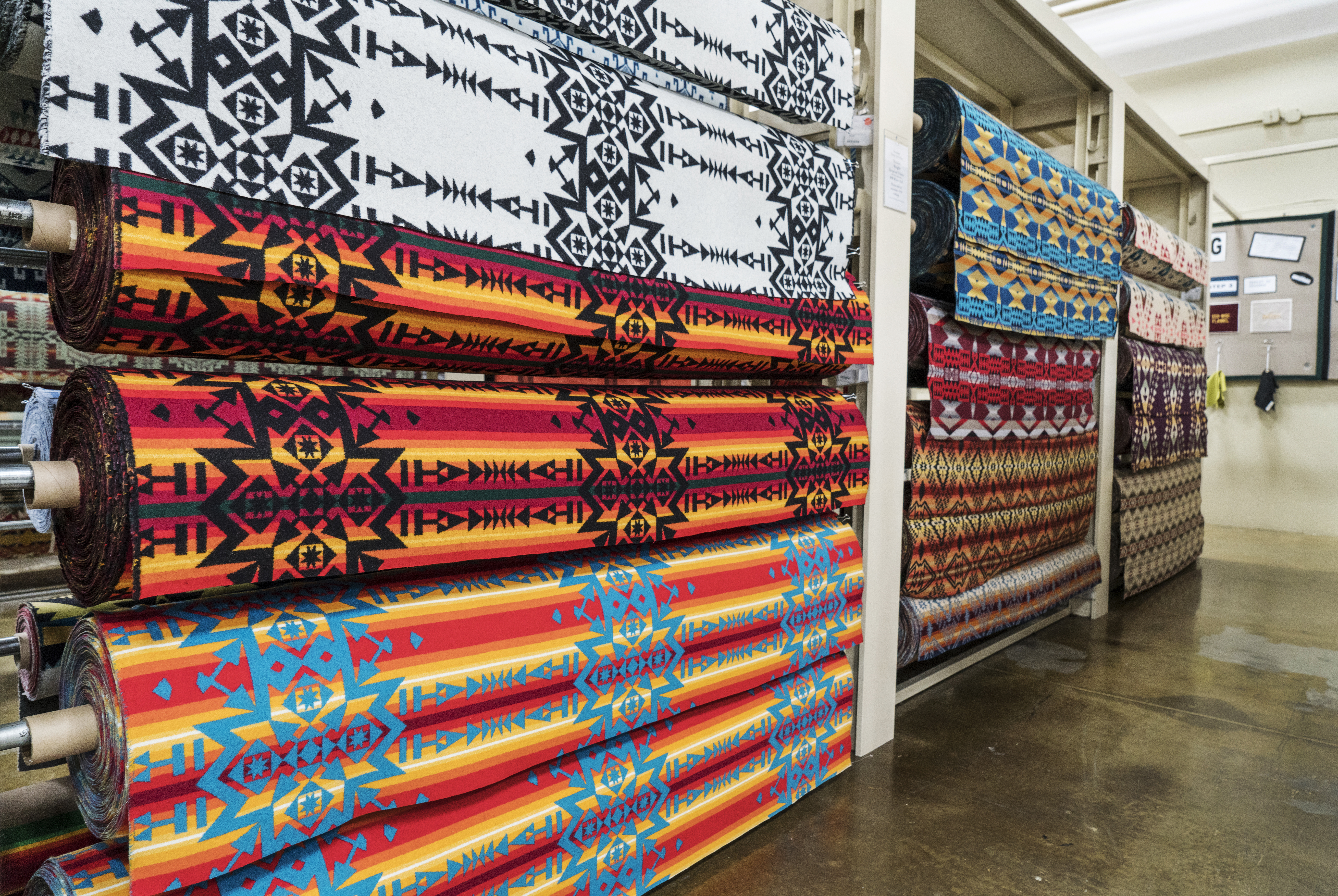 Picture taken in the Woolen Mill Store of rolls of Pendleton wool fabric in white, red, turquoise, blue, brown and yellow patterns.