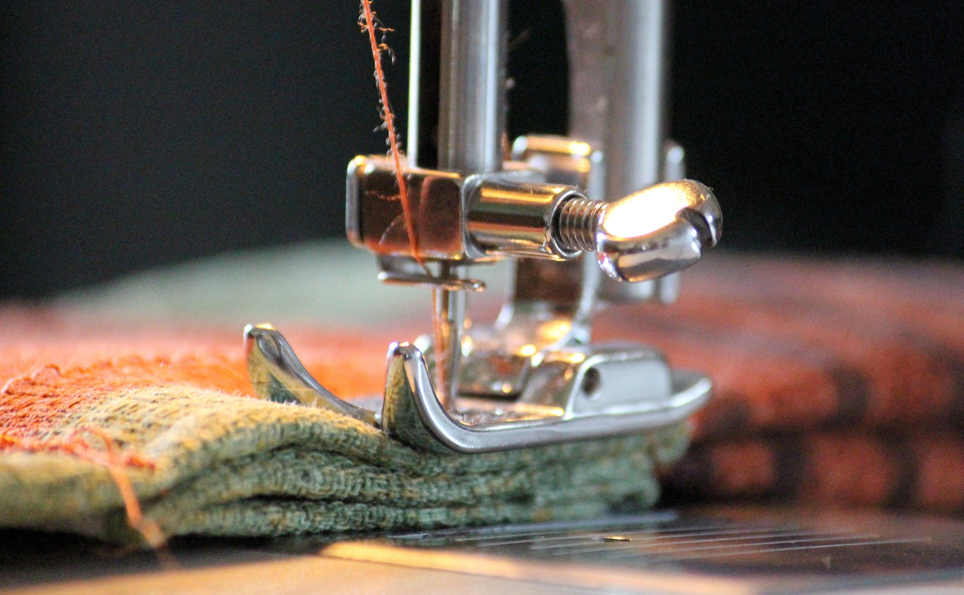 Closeup photo of a sewing machine pressure foor, sewing green and orange fabric, needle threaded with orange thread.
