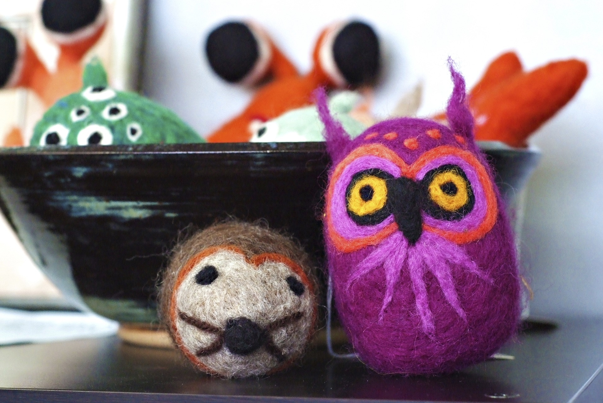felted wool animals next to a black ceramic bowl. brown mouse, purple owl.